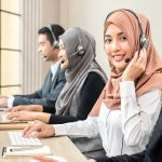 Friendly beautiful Asian muslim woman wearing microphone headset working as customer support operator with team in call center office